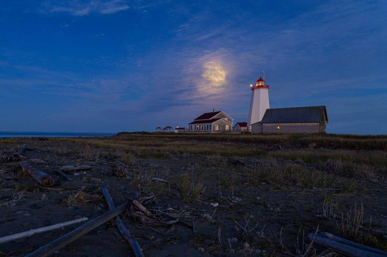 Nearly full moon rising over Miscou Island Lighthouse