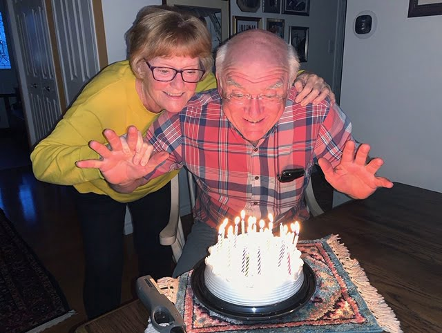 Couple blowing out candles on a birthday cake