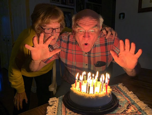 Couple blowing out candles on a birthday cake. Image is not well lit.