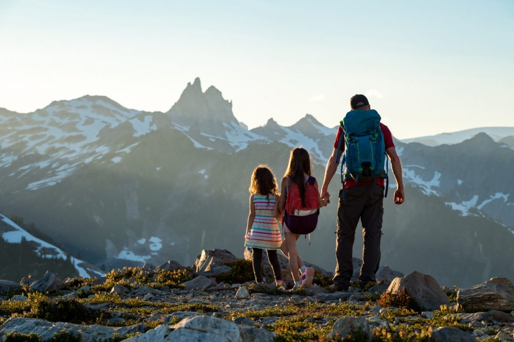 Father and daughters standing on a mountain