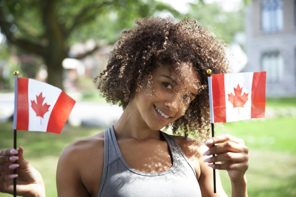 woman holding two small Canadian flagss