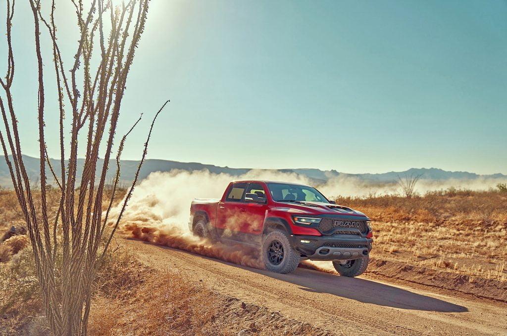 Red truck driving through desert dirt