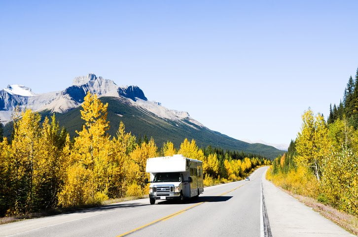 trailer driving in front of mountains