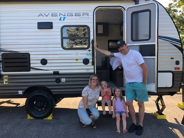 Family in front of a small trailer