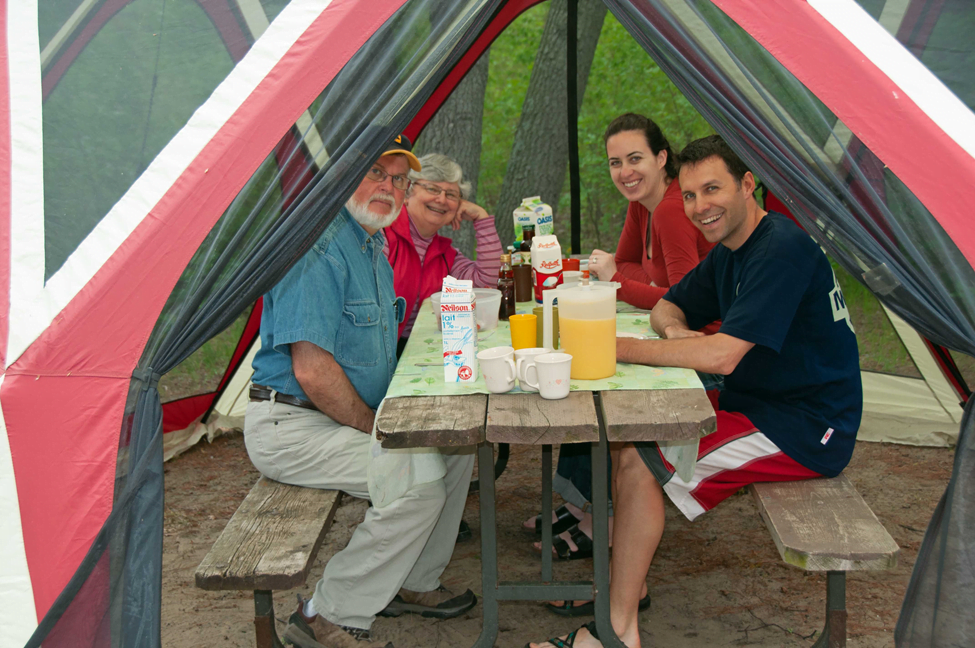 Family sitting at a table on their Ontario provincial parks campsite