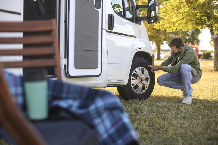 Man checking a tire on a recreational vehicle. About 30 years old Caucasian male.