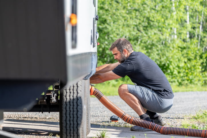 Man Emptying RV Sewer at Dump Station After Camping