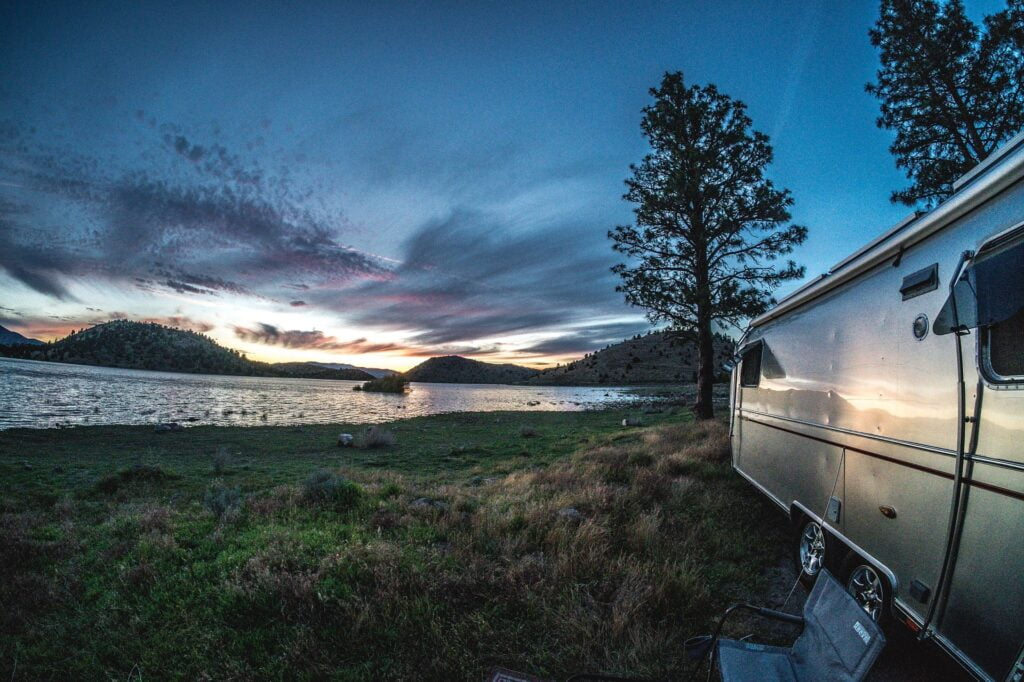 Metal-sided RV with folding chair by a lakeshore at sunset