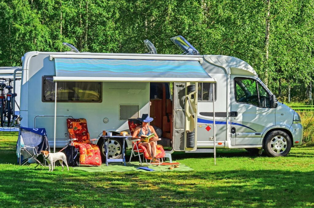 Woman in hat reading a book and sitting under RV awning on the grass with a dog