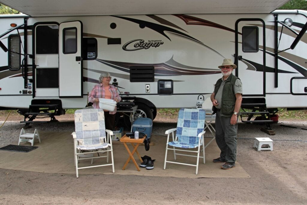 Writer and wife sitting in folding chairs outside their family trailer in a provincial park