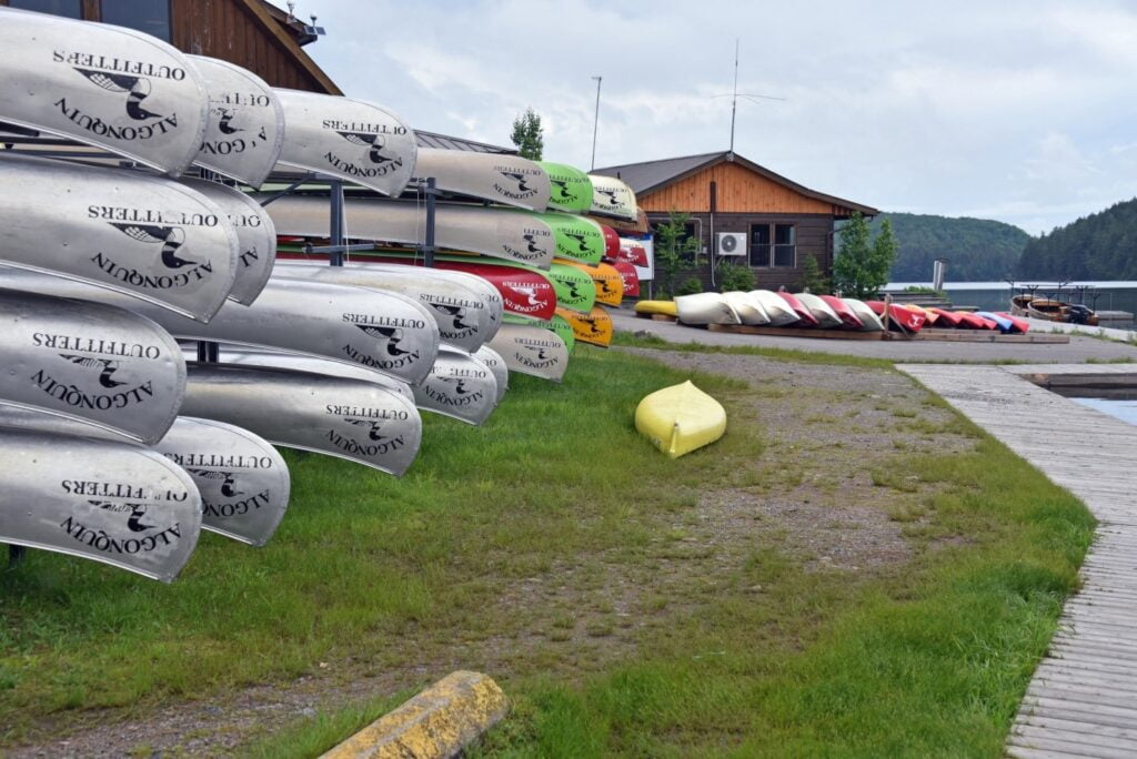 Canoes stacked on grass beside lake at Opeongo Outfitters in Algonquin Provincial Park.