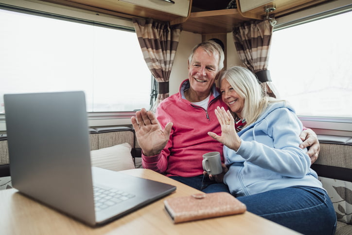 A shot of a senior couple in their campervan on a staycation in Cornwall on a video call on their laptop. Both are smiling and waving to the laptop as they are sat cuddling in.