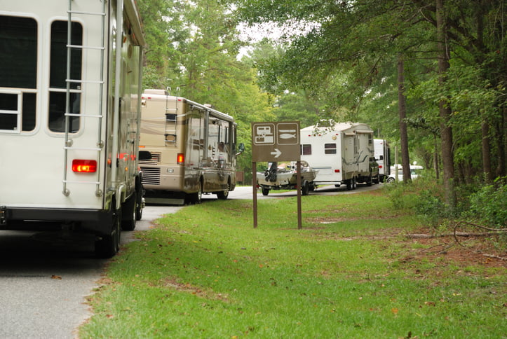 A line of travel trailers and motorhomes in line at campground