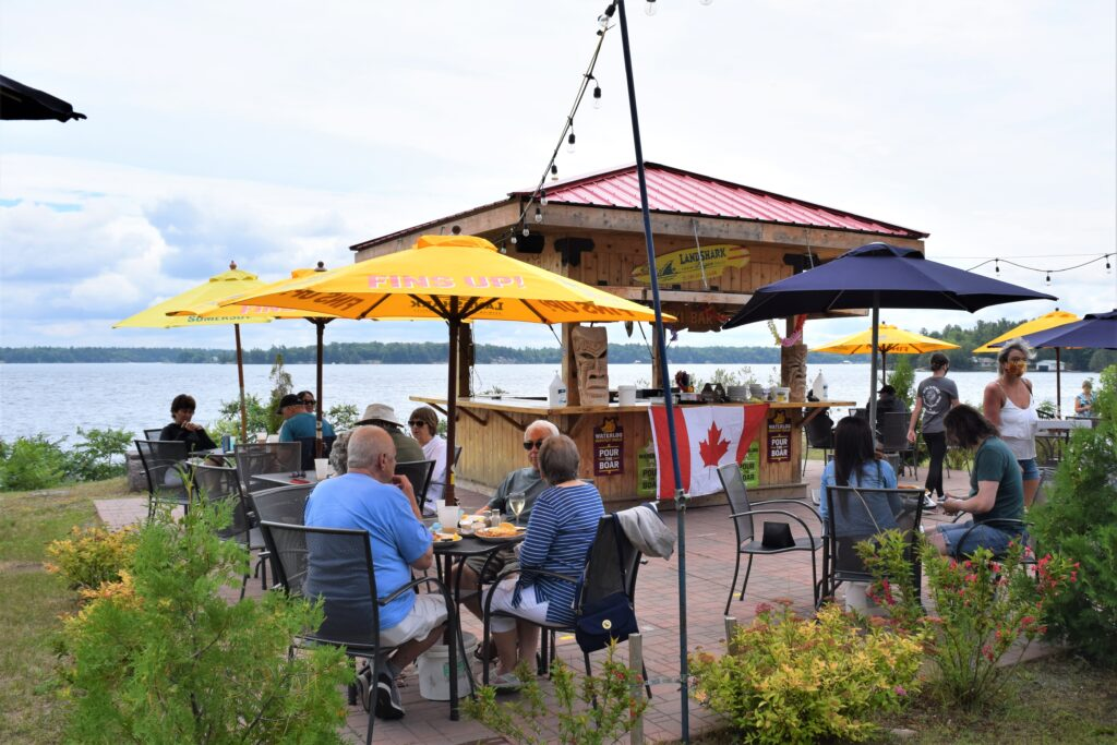On the grass patio, the Tiki bar selling sits surrounded by dining tables
