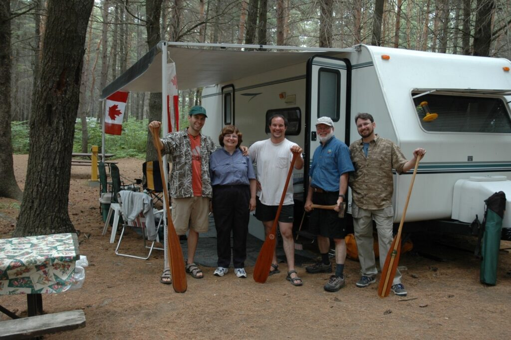 Author with family in front of their 4th generation trailer in a provincial park.