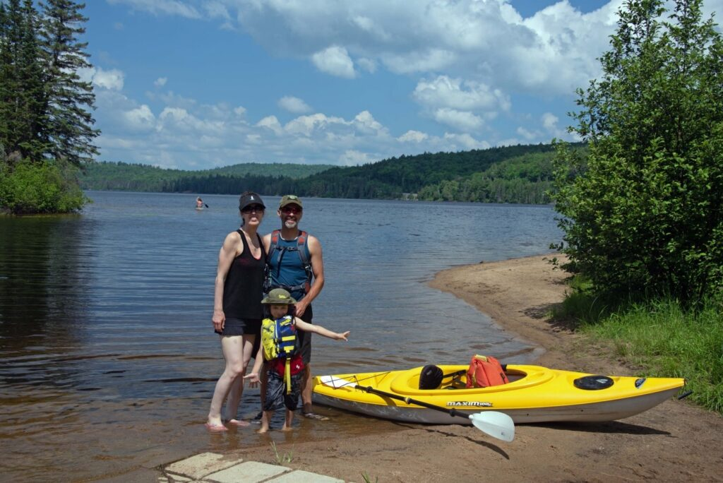 Family of three standing in front of a lake with a yellow kayak