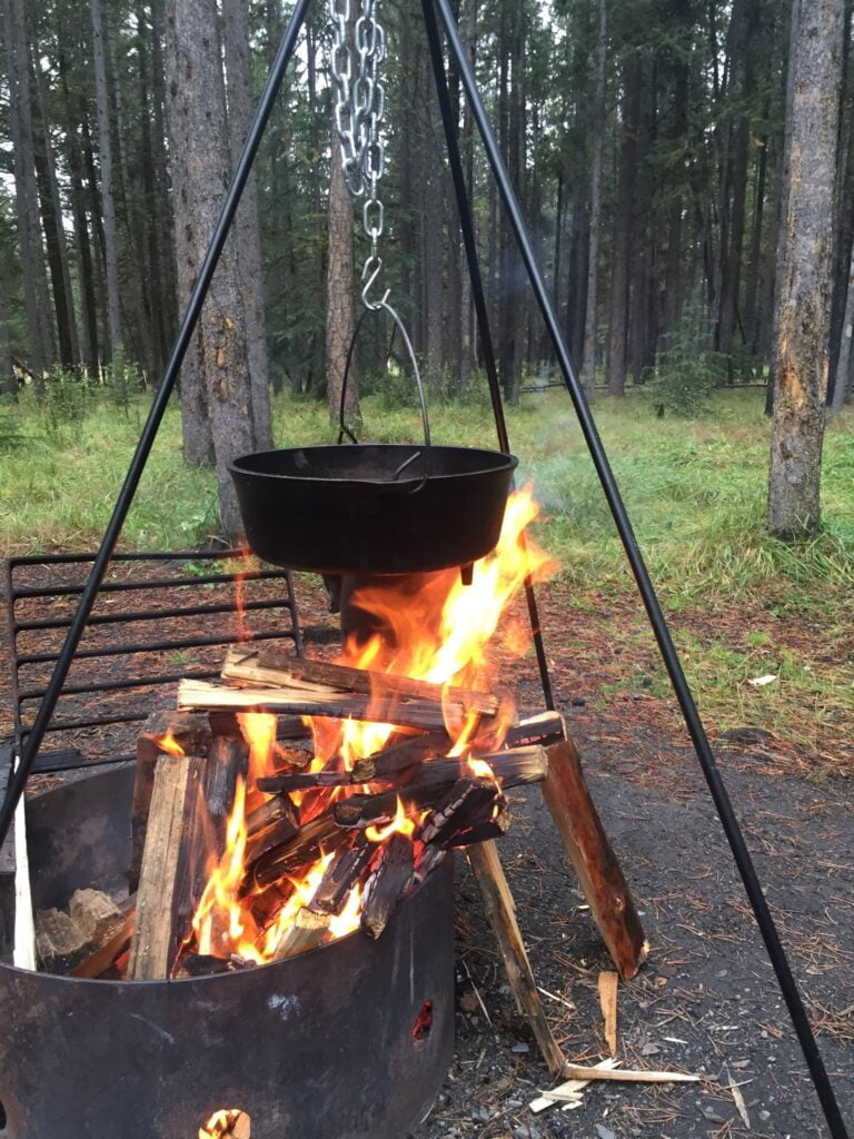 Dutch oven on a tripod cooking over a fire