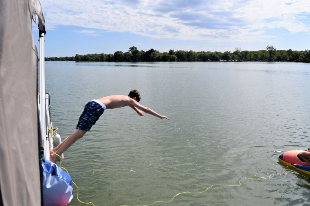 Grandchildren jumping into cold lake water