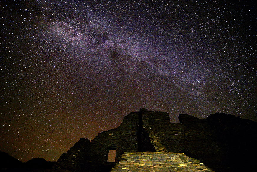 The Milky Way and stars fill the night sky above an Ancestral Puebloan ruin at Chaco Culture National Historical Park, New Mexico, a celestial tourism site.