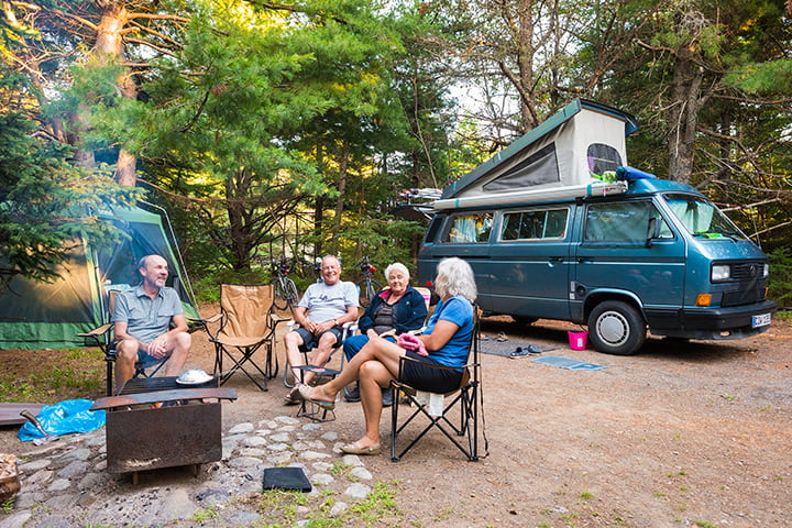 Four adults sitting around a campfire on a trailer campsite at Kouchibouguac National Park.
