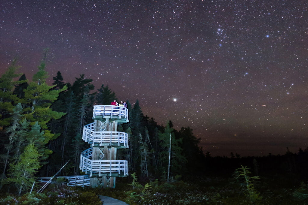 Visitors observing the stars atop the Bog trail tower, and New Brunswick's celestial tourism site, Kouchibouguac National Park, Dark Sky Preserve.
